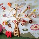 Uma estante em forma de árvore, com galhos são prateleiras cortadas em diferentes medidas.